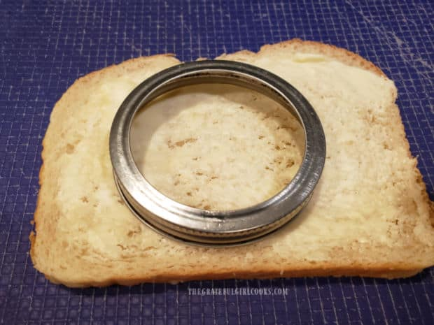 A jar or jar lid is used to cut out a circle in buttered bread.