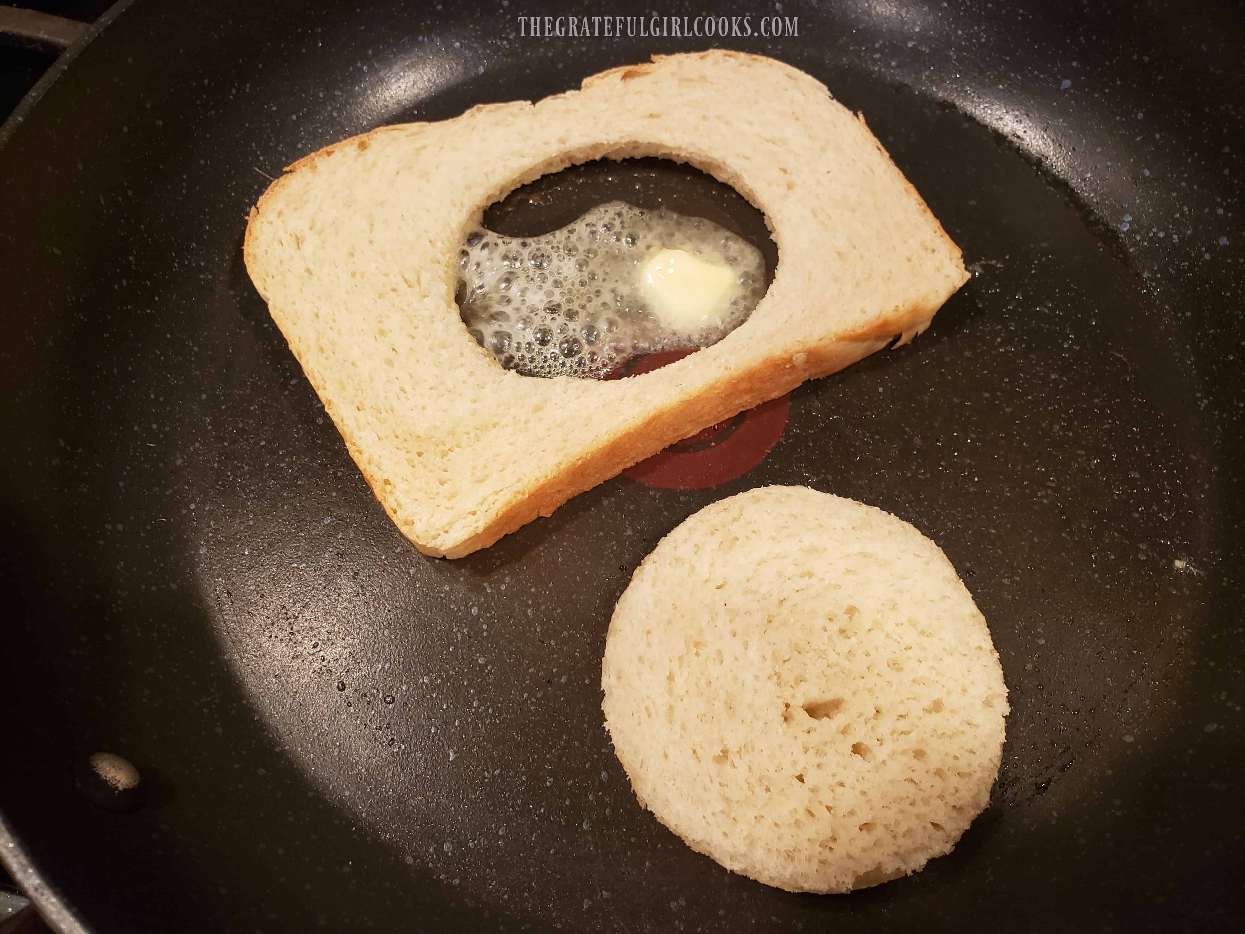 Buttered bread and circle are cooked butter side down until browned.
