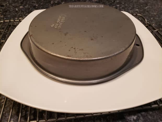 The cake is inverted onto a serving platter, and then the cake pan is removed.