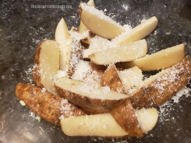 Grated Parmesan cheese is added to, and tossed with the potato wedges.