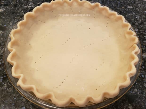 A 9-inch unbaked deep dish pie shell is pricked with a fork before adding ingredients.
