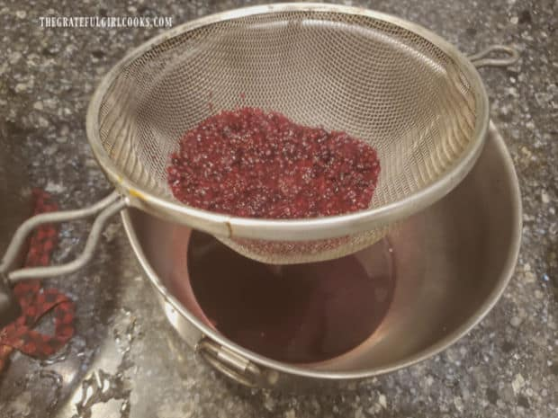 Pressing cooked blackberries through sieve to remove seeds from syrup below.