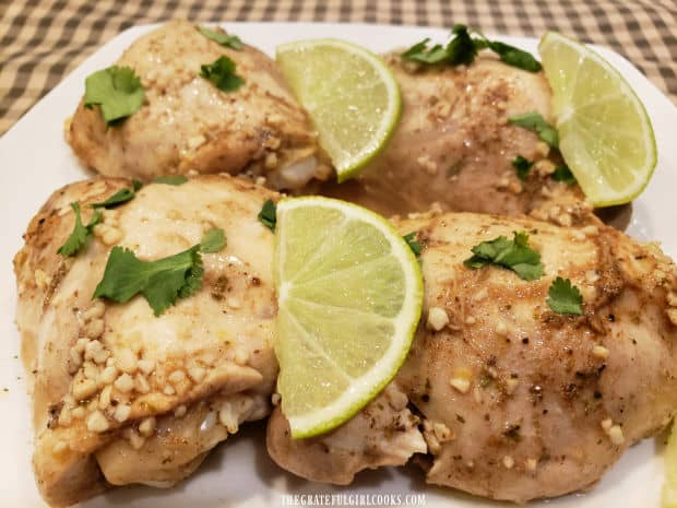 Lime slices and chopped cilantro garnish the garlic lime chicken thighs for serving.
