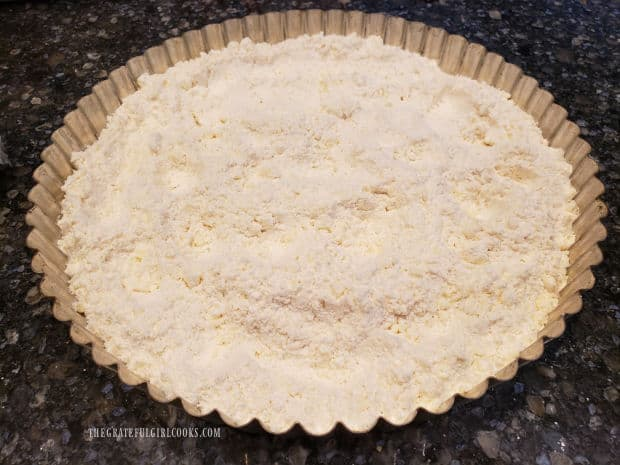 Crumbly crust mixture is poured into a tart pan (with a removable bottom).