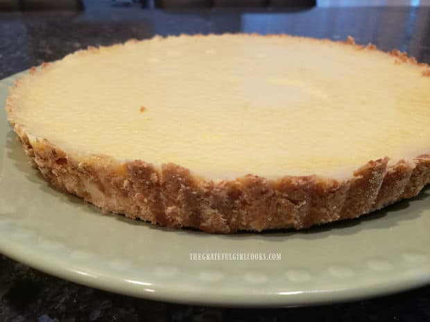 When ready to serve, the chilled lemon cream cheese tart is removed from the pan.