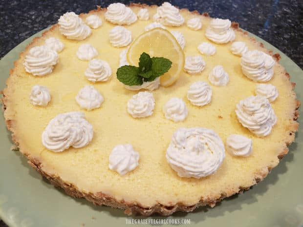 Lemon Cream Cheese Tart, garnished with whipped cream, lemon slice and mint leaf.