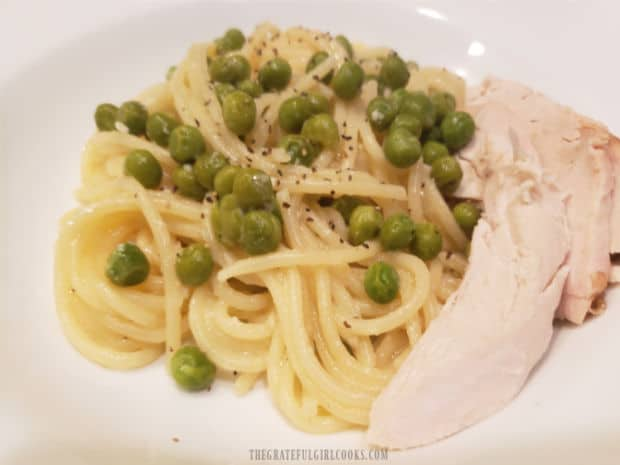 A piece of rotisserie chicken, served on the side of lemon pasta and peas.