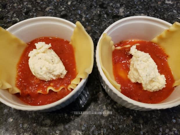 Marinara sauce and a seasoned ricotta cheese mixture is layered into the lasagna bowls.