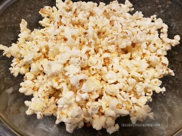 Plain popped popcorn in a bowl, ready for buttery seasoning sauce.