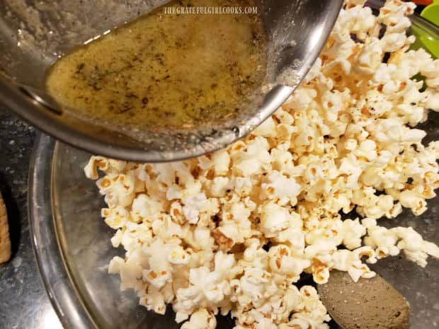 Seasoned butter is drizzled over popped popcorn and stirred to combine.