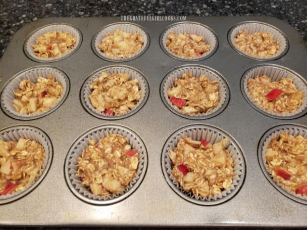 Apple cinnamon baked oatmeal bites batter is evenly divided into paper-lined muffin tins.
