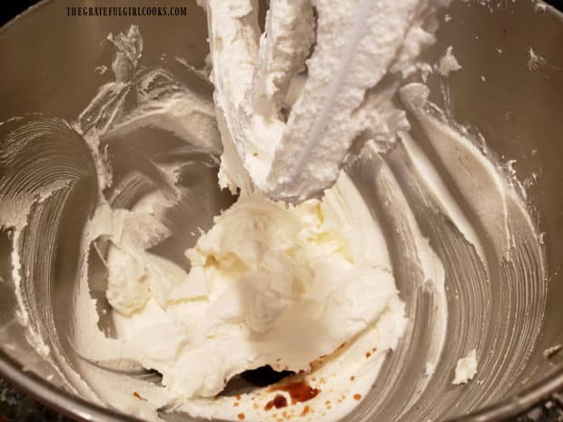 Vanilla extract is added to the frosting mixture in stand mixer.