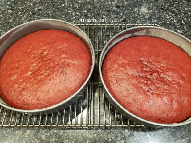 Two pans of red velvet cake cooling on wire racks after baking.
