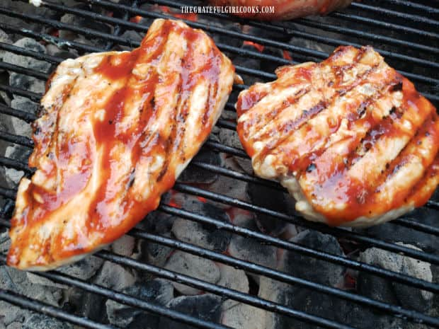 Pieces of chicken brushed with homemade honey BBQ sauce, cooking on the grill.