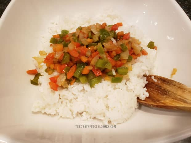 A white bowl with the cooked veggies added on top of cooked white rice.