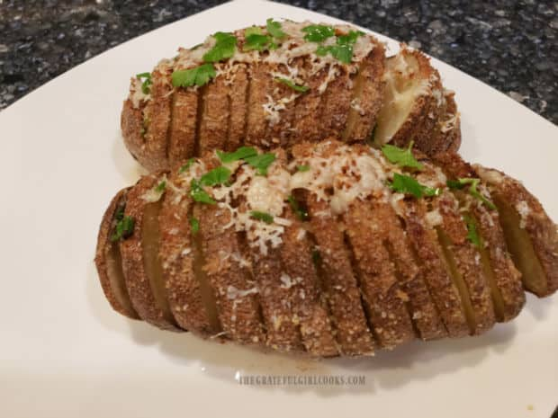 Roasted Hasselback Potatoes, served on a white plate, are a perfect side dish!