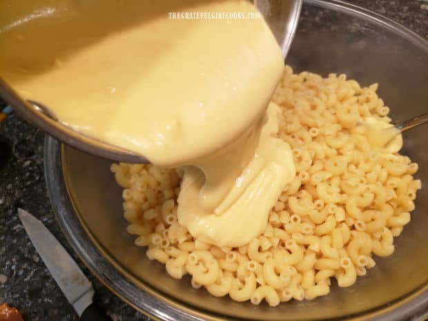 Cheese sauce is added to the cooked pasta, and stirred until combined.