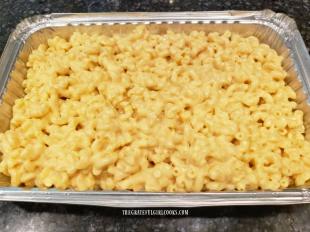 Macaroni and cheese is placed into a greased or buttered baking pan.