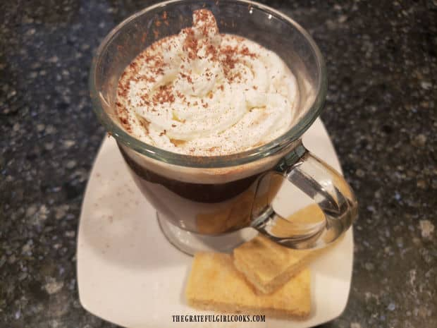 A mug of hot cinnamon mocha coffee is served, topped with whipped cream and cinnamon.