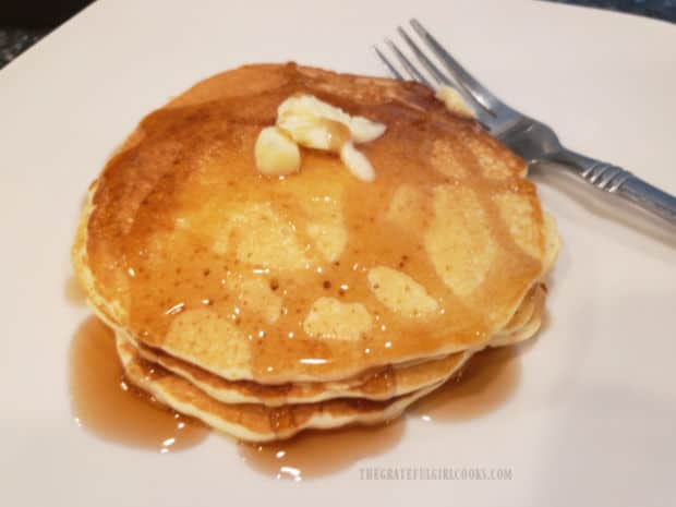 A stack of three easy buttermilk pancakes, topped with butter and maple syrup.