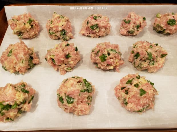 Twelve meatballs are placed on a parchment paper-lined baking sheet to bake.
