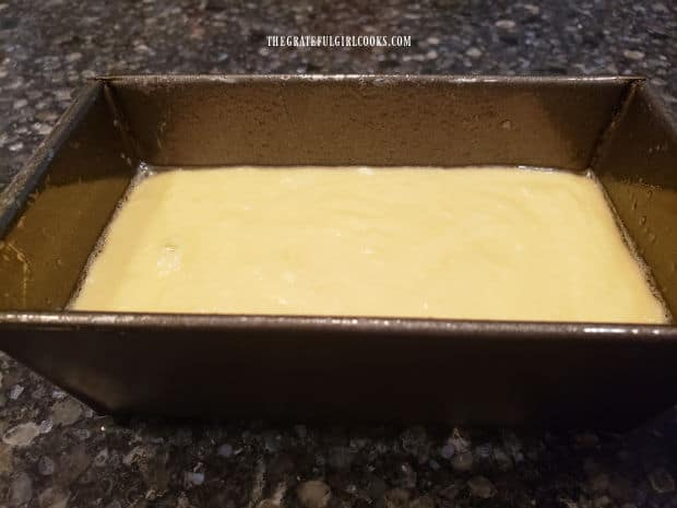 The batter for the mini-loaf pound cake is poured into a greased loaf pan, for baking.