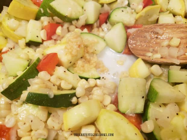 Minced garlic and a small amount of milk are added to the cooking veggies.