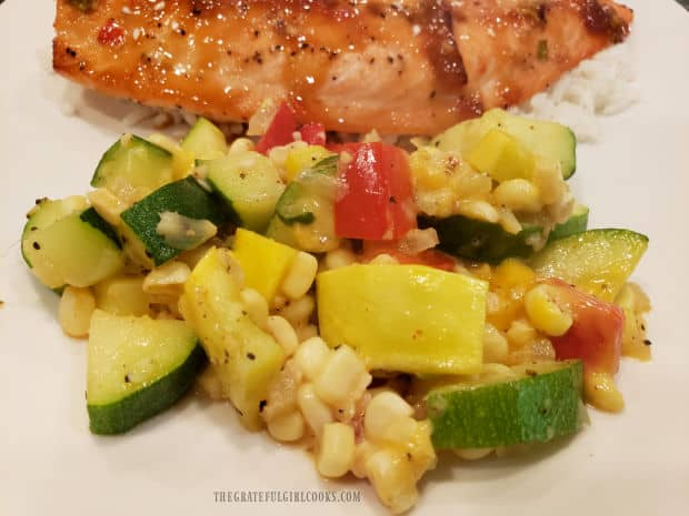 A serving from the TexMex Zucchini Squash skillet, placed on a plate with rice and salmon.