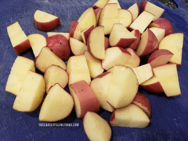 The unpeeled red potatoes are cut into bite sized chunks before seasoning.