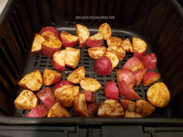 The potatoes are placed in an air fryer basket in a single layer.
