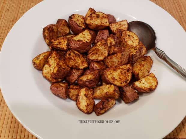 A white bowl, full of air fryer Cajun spuds, ready to eat!