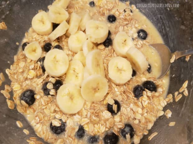 Sliced bananas are gently stirred into the blueberry banana baked oatmeal mixture.