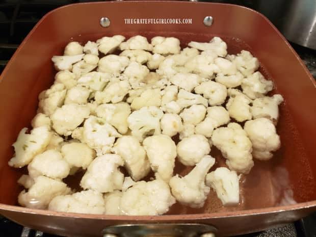 Boiling the cauliflower florets until tender.
