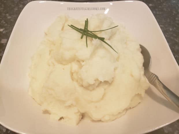 A serving bowl filled with creamy garlic mashed cauliflower, ready to eat.