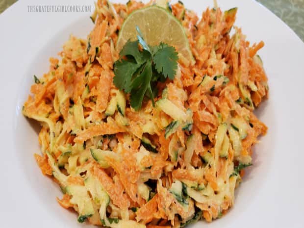 Zucchini Carrot Lime Coleslaw is garnished with lime wedge and cilantro sprigs to serve.