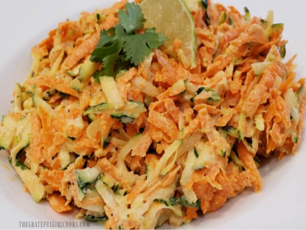 Delicious zucchini carrot lime coleslaw is served in a white bowl, with cilantro/lime garnish.